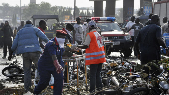Rescue workers work to recover victims at the site of a blast at the Nyanya Motor Park, about 16 kilometers (10 miles) from the center of Abuja, Nigeria, Monday, April 14, 2014. An explosion blasted through a busy commuter bus station on the outskirts of Abuja before 7 a.m. (0600 GMT) Monday as hundreds of people were traveling to work. (AP Photo/Gbemiga Olamikan)