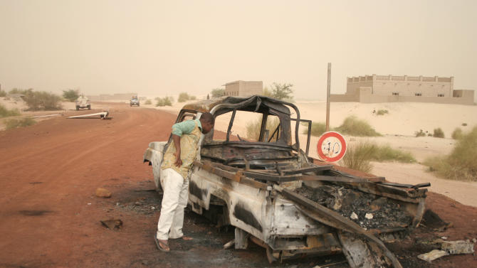 In this photo taken Thursday Jan. 31, 2013, a man takes a close look at a burned-out truck in Timbuktu, Mali.  Islamic militants fled from the area when French special forces parachuted in to liberate the city of Timbuktu several days ago.  (AP Photo/Harouna Traore)