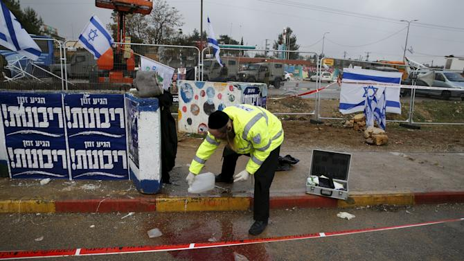 Zaka emergency personnel clean a bloodstain from the ground at the scene where Israeli security forces shot dead a Palestinian assailant who tried to stab a man at Gush Etzion junction, near a West Bank settlement