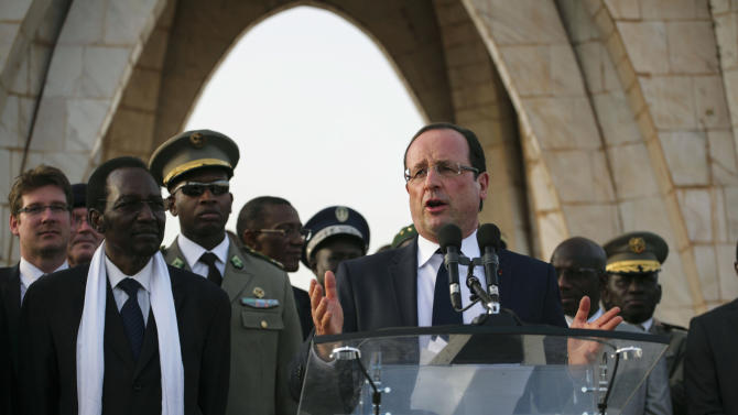 French President Francois Hollande, with Mali's President Dioncounda Traore, second from left, at his side, gives an address at Independence Place in central Bamako, Mali Saturday, Feb. 2, 2013. The French president was greeted by thousands of cheering supporters as he visited the embattled city of Timbuktu earlier Saturday, making a triumphant stop six days after French forces parachuted in to liberate the fabled city from the radical Islamists occupying it.(AP Photo/Thomas Martinez)