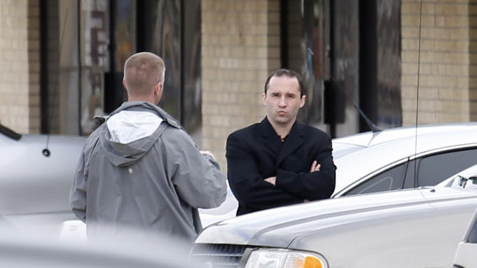 Everett Dutschke, right, confers with a federal agent near the site of a martial arts studio he once operated, Wednesday, April 24, 2013 in Tupelo, Miss. The property was being searched in connection with the investigation into poisoned letters mailed to President Barack Obama and others. Dutschke has not been arrested or charged. (AP Photo/Rogelio V. Solis)