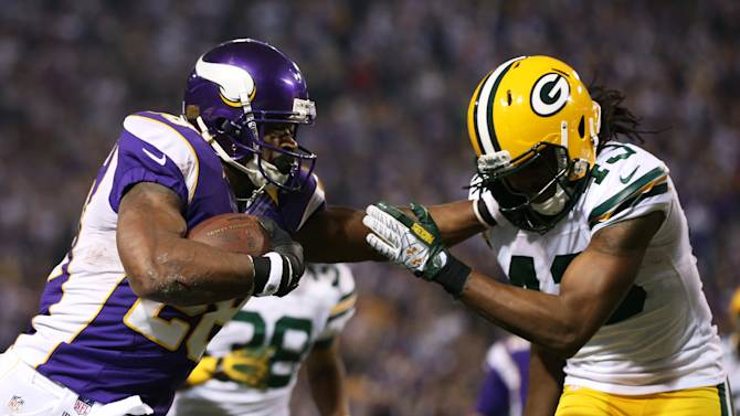 Minnesota Vikings running back Adrian Peterson, left, tries to break a tackle by Green Bay Packers free safety M.D. Jennings, right, during the second half of an NFL football game Sunday, Dec. 30, 2012, in Minneapolis. (AP Photo/Jim Mone)