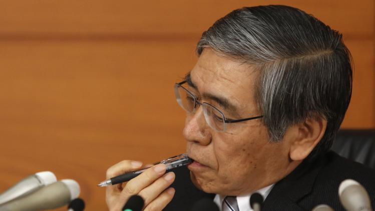 Bank of Japan Governor Kuroda bites on his pen as he listens to questions from a reporter during a news conference at the BOJ headquarters in Tokyo