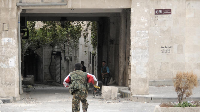 In this Tuesday, Nov. 6, 2012 photo, a Syrian rebel runs for cover to avoid Syrian Army sniper fire on Sabaa al- ahriat street, in the Old City of Aleppo, Syria.(AP Photo/Monica Prieto)