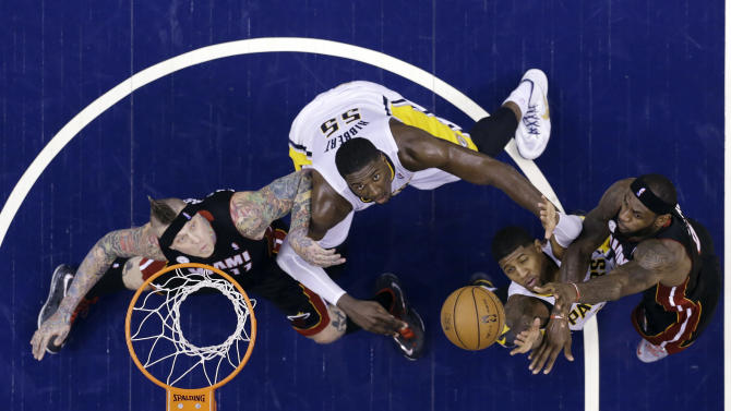 Miami Heat's LeBron James, right, puts up a shot over Indiana Pacers defenders Paul George, Roy Hibbert (55) as Heat's Chris Andersen, left, watches during the first half of Game 3 of the NBA Eastern Conference basketball finals in Indianapolis, Sunday, May 26, 2013. (AP Photo/Michael Conroy)