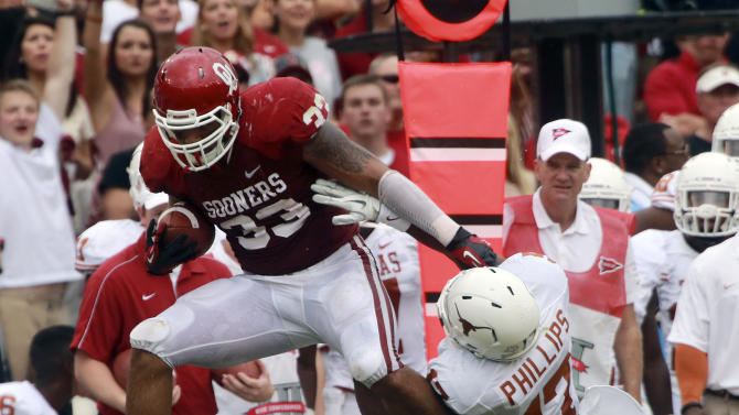 Oklahoma fullback Trey Millard (33) breaks a tackle against Texas cornerback Adrian Phillips (17) and defensive back Mykkele Thompson (2) during the first half of an NCAA college football game at the Cotton Bowl Saturday, Oct. 13, 2012, in Dallas. (AP Photo/Michael Mulvey)