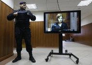A policeman watches band member Nadezhda Tolokonnikova speaking on a TV screen in a hall outside a court room of the Moscow City Court where three members of the punk band Pussy Riot are set to make their case before a Russian appeals court that they should not be imprisoned, in Moscow, Wednesday. Oct. 10, 2012. Their impromptu performance inside Moscow&#39;s main cathedral in February came shortly before Putin was elected to a third term. The three women were convicted in August of hooliganism motivated by religious hatred and sentenced to two years in prison. (AP Photo/Sergey Ponomarev)