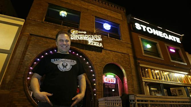 """Jeff Call, owner of the Stonegate pizza-and-rum bar, poses for a photo in front of his business, Saturday, March 2, 2013, in Tacoma, Wash. Call charges patrons a small fee to become a member of the private second-floor club in the lounge area upstairs, which allows """"vaporizing"""" marijuana, a method that involves heating the marijuana without burning it. Last fall, Washington and Colorado became the first states to legalize marijuana use for adults over 21. (AP Photo/Ted S. Warren)"""