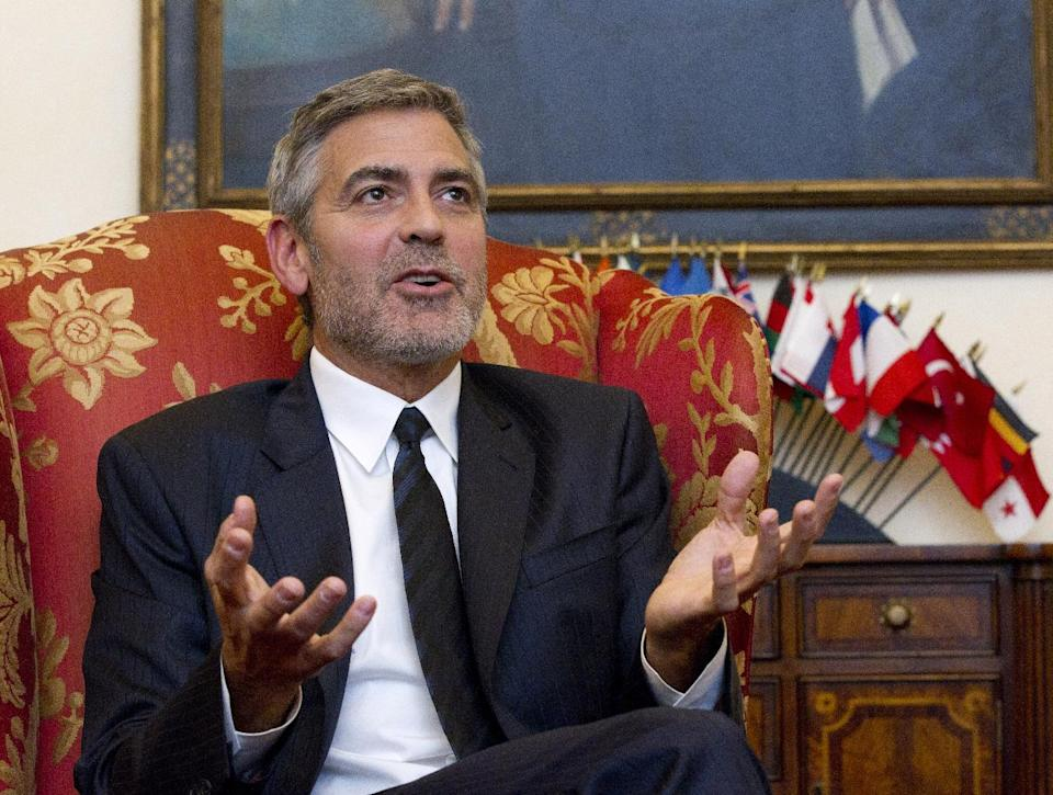 Actor George Clooney gestures during an interview with The Associated Press, and other news organizations, Wednesday, March 14, 2012, on Capitol Hill in Washington. Clooney was to testify before the Senate Foreign Relations Committee hearing on Sudan. (AP Photo/Manuel Balce Ceneta)