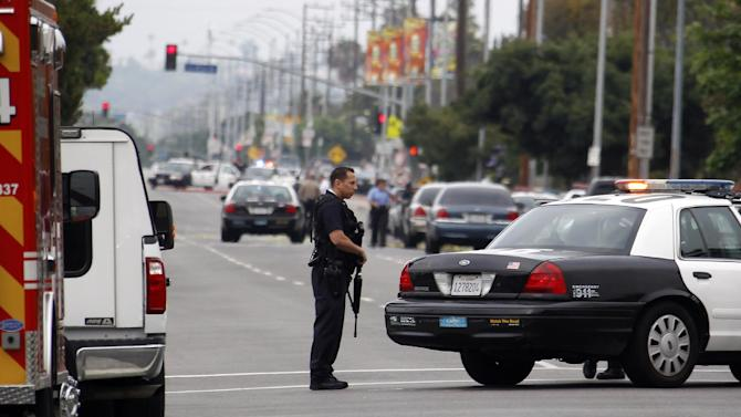 Los Angeles police officers close off and search a city street after two police officers were shot and wounded in an attack outside a police station in the Mid-City area of Los Angeles on Tuesday June 25, 2013. A black-clad gunman ambushed two detectives returning to a police station early Tuesday, but they received only minor injuries and were helping in the hunt for the attacker, police said. (AP Photo/Nick Ut)