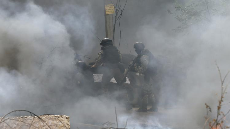 Ukrainian security force officers enter a checkpoint set on fire and left by pro-Russian separatists near Slaviansk
