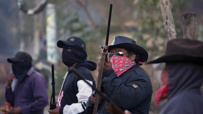 Armed and masked men guard a roadblock at the entrance to the community of El Pericon near Ayutla, early Saturday, Jan. 19, 2013.  Hundreds of  men in the southern Mexico state of Guerrero have taken up arms to defend their villages against drug gangs, a vigilante movement born of frustration at extortion, killings and kidnappings in a region wracked by violence. (AP Photo/Dario Lopez-Mills)