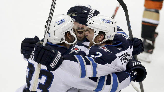 Winnipeg Jets defenseman Adam Pardy, right, celebrates with Dustin Byfuglien, left, and Mathieu Perreault after scoring against the Anaheim Ducks during the second period of Game 2 of a first-round NHL hockey playoff series in Anaheim, Calif., Saturday, April 18, 2015. (AP Photo/Chris Carlson)