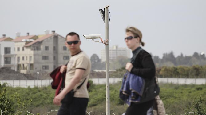 People walk past a security camera installed outside the Olympic Park that is under construction for the  the 2014 Winter Games, in the Black Sea resort of Sochi, Russia, Tuesday, April 16, 2013. Russian sports officials said Tuesday they will beef up security at sports events and the Sochi 2014 Winter Games in the wake of deadly explosions at Boston's marathon that killed three people, and injured over 140 others. (AP Photo/Artur Lebedev)