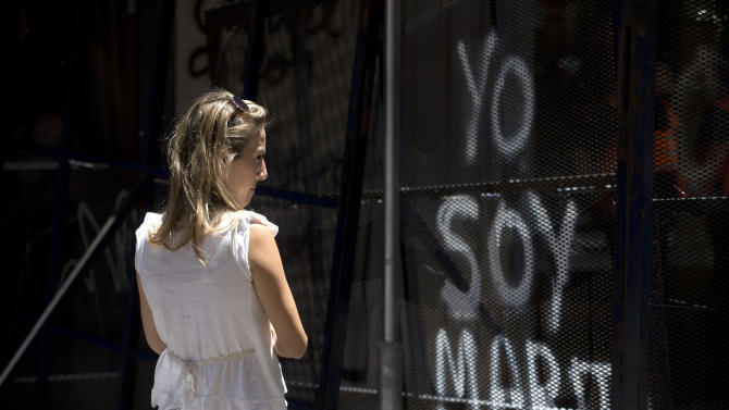 """A woman looks at graffiti that reads in Spanish """"I'm Marita"""" written by protesters on the fence protecting the building used by government representatives of Argentina's Tucuman province during a demonstration in Buenos Aires, Argentina, Wednesday, Dec. 12, 2012. Activists are protesting the Tuesday decision by judges that found all defendants innocent in a high-profile case of an Argentine woman, Maria de los Angeles """"Marita"""" Veron, who was allegedly kidnapped and forced into prostitution a decade ago in Tucuman. (AP Photo/Victor R. Caivano)"""