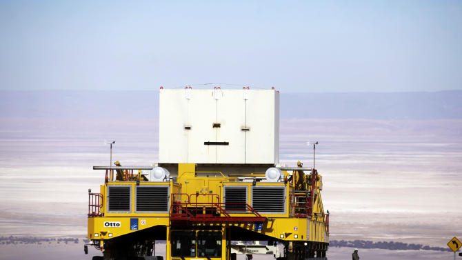 In this Sept. 27, 2012 photo, a transporter truck lifts a box that weight as much as an antenna, as part of a transport test at of one of the worlds largest astronomy projects, the Atacama Large Millimeter/submillimeter Array (ALMA) near Chajnator in the Atacama desert in northern Chile. The lack of humidity, low interference from other radio signals and closeness to the upper atmosphere in this remote plateau high above Chile's Atacama desert, is the perfect spot for the ALMA, the earth's largest radio telescope, which is on track to be completed in March. (AP Photo/Jorge Saenz)