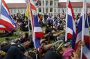 Anti-government protesters rest after breaking into the compound of the Royal Thai Army headquarters in Bangkok