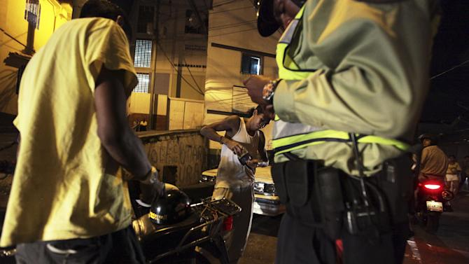 In this photo taken Friday, June 1, 2012, a Baruta's municipal police officer checks the identification of two men while on night patrol in Caracas,Venezuela. The government says more than 14,000 people were killed in Venezuela last year, giving the country a murder rate of 50 per 100,000 people and making it one of the most violent countries in Latin America and the world. The murder rate has more than doubled since 1998, when Venezuela's President Hugo Chavez was first elected. (AP Photo/Fernando Llano)