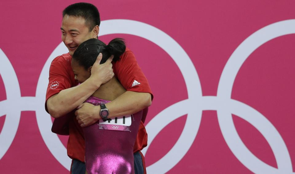 U.S. gymnast Gabrielle Douglas is hugged by coach Liang Chow after her final and deciding performance on the floor during the artistic gymnastics women's individual all-around competition at the 2012 Summer Olympics, Thursday, Aug. 2, 2012, in London. (AP Photo/Gregory Bull)