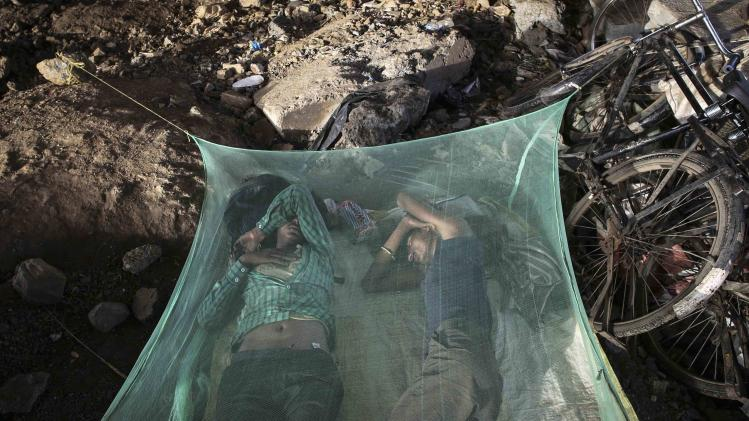 Migrant workers sleep under a mosquito net beneath an overpass in Mumbai