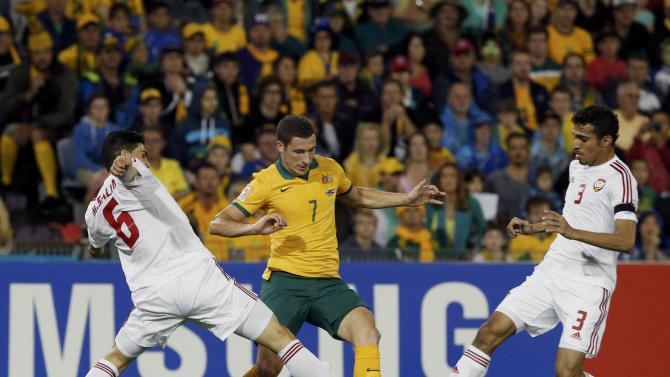 Australia's Mathew Leckie fights for the ball with UAE's Mohanad Salem and Walid Abbas during their Asian Cup semi-final soccer match at the Newcastle Stadium in Newcastle