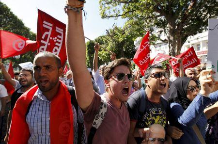 Protesters shout slogans during a demonstration against the economic reconciliation bill