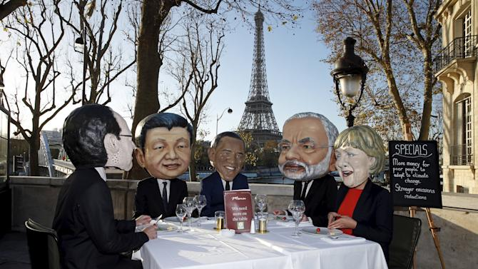 Activists of global anti-poverty charity Oxfam, wearing masks depicting Hollande, Xi, Obama, Modi and Merkel stage a protest ahead of COP21 summit in Paris