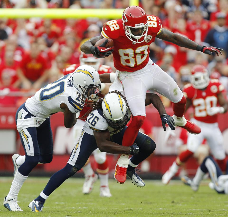 Kansas City Chiefs wide receiver Dwayne Bowe (82) is tackled by San Diego Chargers strong safety Atari Bigby (26) and cornerback Antoine Cason (20) during the first half of an NFL football game at Arrowhead Stadium in Kansas City, Mo., Sunday, Sept. 30, 2012. (AP Photo/Ed Zurga)