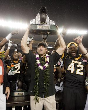 Southern Mississippi head coach Larry Fedora holds up the 2011 Hawaii Bowl trophy after an NCAA college football game Saturday, Dec. 24, 2011, in Honolulu. Southern Mississippi defeated Nevada 24-17 to win the 2011 Sheraton Hawaii Bowl. (AP Photo/Eugene Tanner)
