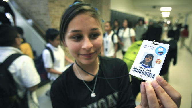 "In this Oct. 1, Tira Starr, an 8th grader at Anson Jones Middle School, shows her ID badge as students change classes in San Antonio, Texas. The San Antonio school district's website was hacked over the weekend to protest its policy requiring students to wear microchip-embedded cards tracking their every move on campus. A teenager purportedly working with the hacker group Anonymous said in an online statement that he took the site down because the Northside school district ""is stripping away the privacy of students in your school."" All students at John Jay High School and Anson Jones Middle School are required to carry identification cards embedded with a microchip. They are tracked by the dozens of electronic readers installed in the schools' ceiling panels.  (AP Photo/San Antonio Express-News, Bob Owen)   RUMBO DE SAN ANTONIO OUT; NO SALES"