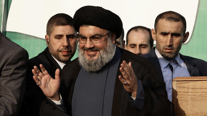 FILE - In this Monday, Sept. 17, 2012 file photo, Hezbollah leader Sheik Hassan Nasrallah, center, waves to his supporters, in the southern suburb of Beirut, Lebanon. The leader of Lebanon's Hezbollah says Syrian rebels will not be able to defeat President Bashar Assad's regime, while strongly suggesting his Iranian-backed militant group could intervene on the government's side if the need arises. (AP Photo/Hussein Malla, File)