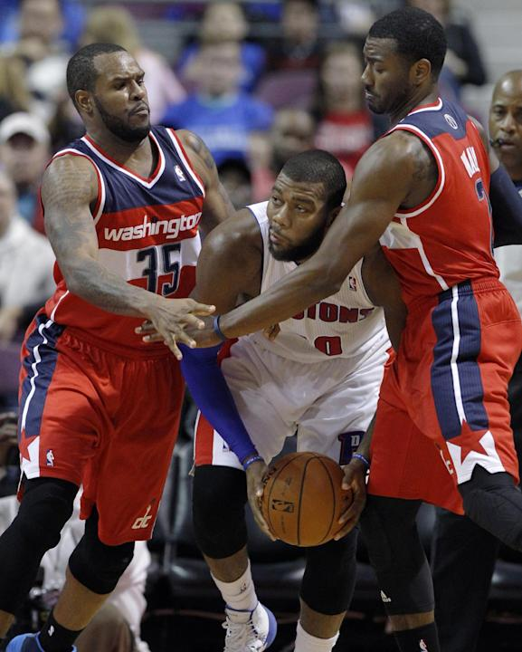Detroit Pistons center Greg Monroe, center, is trapped in a corner by Washington Wizards forward Trevor Booker (35) and guard John Wall during the first half of a preseason NBA basketball game Tuesday