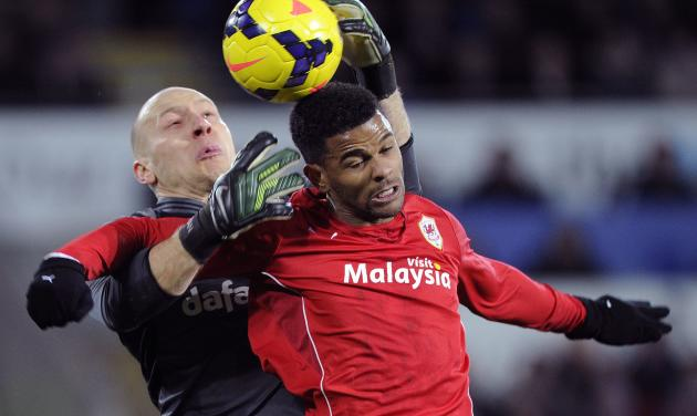 Aston Villa's Brad Guzan challenges Cardiff City's Fraizer Campbell during their English Premier League soccer match at Cardiff City Stadium in Cardiff