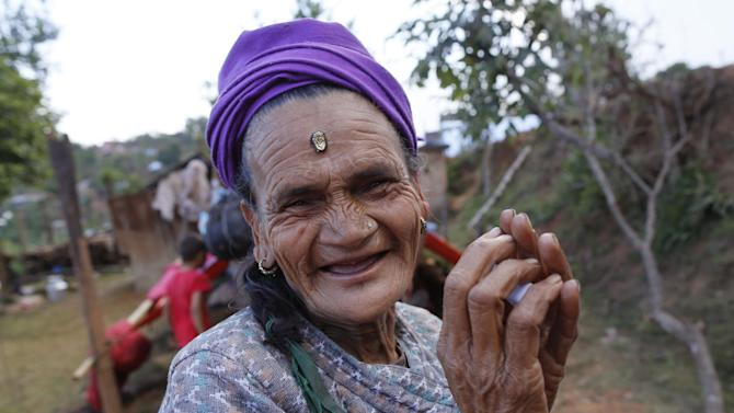 In this photo taken on Saturday, May 2, 2015, Loysyanri Khanal, 78, smiles outside of her home in the destroyed village of Pokharidanda, near the epicenter of the April 25 massive earthquake, in the Gorkha District of Nepal.  A week after the massive 7.8-magnitude earthquake hit Nepal near here, in the central Gorkha District, people in many villages along the roads have stopped waiting for the government to bring help.  Their needs are vast, but Nepal is so short on relief supplies and the means to distribute them that officials are focusing on the farthest flung reaches of the remote Himalayas.  (AP Photo/Wally Santana)