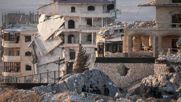 In this Sunday, Sept. 29, 2013 photo, Syrian opposition fighters take cover during exchange of fire with government forces in Telata village, a frontline located at the top of a mountain in the Idlib, northwest province countryside of Syria. (AP Photo)