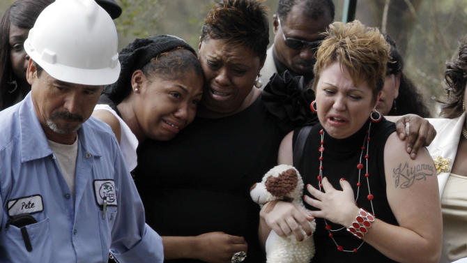 Surrounded by family, Tiffany Dickerson, right, cries at the gravesite of her son Shomari Dickerson, Thursday, March 3, 2011, in Houston. The 3-year-old died in a day care fire Feb. 24. (AP Photo/Pat Sullivan)