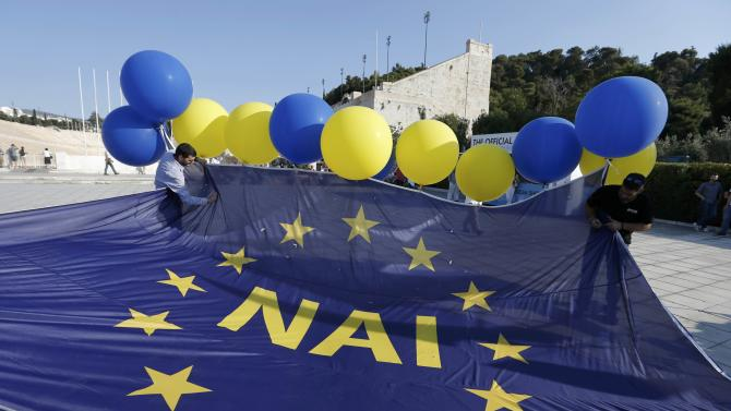 Men prepare large EU flag printed with the word 'yes' to be floated into air prior to the pro-Euro rally at Panathenean stadium in Athens