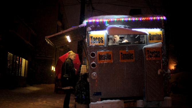 Asrael Velazquez, right, prepares an order for Amelie, who declined to provide her last name, of Germany, at the Casa Mexicana food cart early Saturday, Feb. 9, 2013, in the Williamsburg section of the Brooklyn borough of New York. Snow began falling across the Northeast on Friday, ushering in what was predicted to be a huge blizzard. (AP Photo/Jeffrey Furticella)
