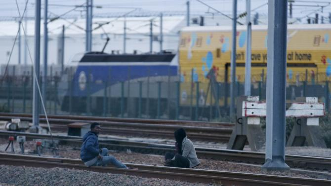 Migrants sit on rails as they make their way along train tracks in an attempt to access the Channel Tunnel in Frethun, near Calais