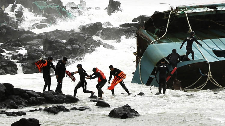 A Chinese fisherman wearing an orange life vest, fourth from left, is rescued by South Korean coast guard officers from a Chinese ship in Jeju,  South Korea, Tuesday, Aug. 28, 2012. A powerful typhoon pounded South Korea with strong winds and heavy rain Tuesday, while the nation's coast guard battled rough seas in a race to rescue fishermen on two Chinese ships that slammed into rocks off the southern coast. (AP Photo/Newsis, Kang Jae-nam) KOREA OUT