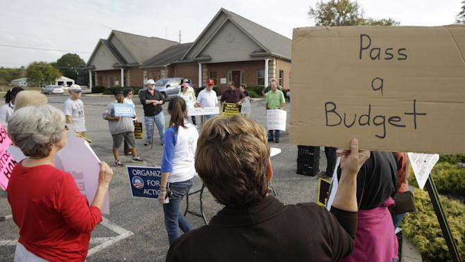 Protesters organize outside the offices of Speaker John Boehner (R-Ohio), Tuesday, Oct. 15, 2013, in West Chester, Ohio. The government shutdown is entering its third week. (AP Photo/Al Behrman)