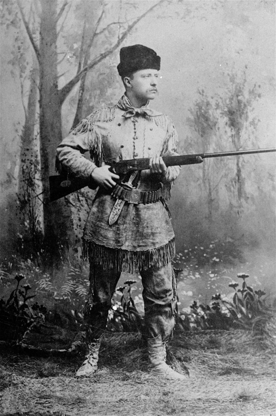 "FILE - In this undated photo provided by Harvard University Press, President Theodore Roosevelt, posing as an ""outdoorsman,"" points his rifle during a studio photo session.   AP Photo/Harvard University Press)"