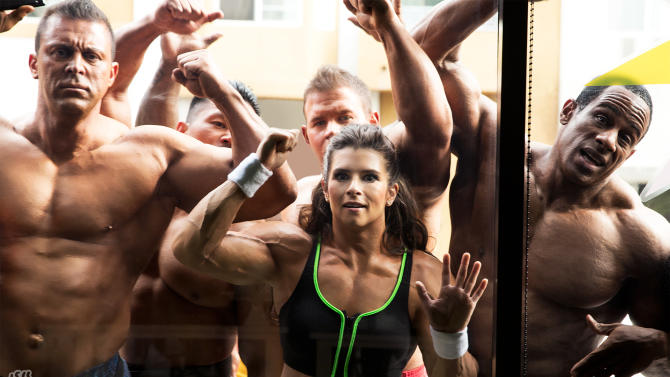 In this image released by GoDaddy.com on Wednesday, Jan. 22, 2014, NASCAR driver Danica Patrick, center, wearing a muscle suit, appears with bodybuilders in an upcoming Super Bowl commercial shot on location in Long Beach, Calif. The commercial is expected to air during the second half of NFL football's Super Bowl XLVIII on Sunday, Feb. 2. (AP Photo/GoDaddy.com)