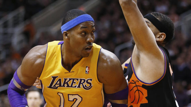 Los Angeles Lakers' Dwight Howard (12) backs down Phoenix Suns' Jared Dudley during the first half on an NBA basketball game, Wednesday, Jan. 30, 2013, in Phoenix. (AP Photo/Matt York)