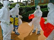 World Health Organization officials wear protective gear as they prepare to enter Kagadi Hospital in Uganda's western Kibale district in July 2012. US Secretary of State Hillary Clinton arrived in Uganda Thursday to discuss regional security with the staunch ally on a trip that also takes her to South Sudan for talks on its border dispute with Khartoum