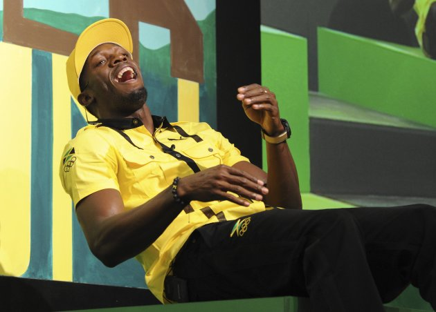 Jamaican sprinter Usain Bolt laughs during a team news conference in east London, July 26, 2012. REUTERS/Paul Hackett