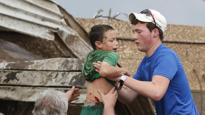 In this Monday, May 20, 2013 photo, Xavier Delgado is carried from the rubble of Plaza Towers Elementary school following a tornado in Moore, Okla. Impaled by a ceiling tile, Delgado needed seven interior and seven exterior stitches. When school begins again Friday, Aug. 16, 2013, Plaza Towers students will go to a renovated building on the junior high campus. (AP Photo/Sue Ogrocki)