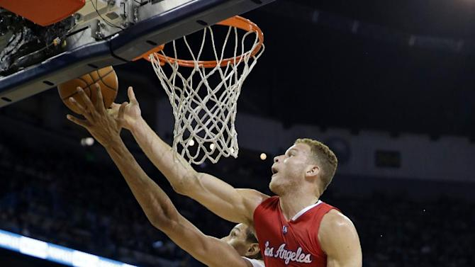 Los Angeles Clippers forward Blake Griffin (32) leaps for a rebound against New Orleans Pelicans center Alexis Ajinca, center, during the first half of an NBA basketball game in New Orleans, Friday, Jan. 30, 2015. (AP Photo/Gerald Herbert)