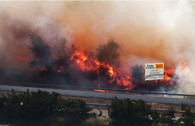 Flames ravage the forest near the highway in La Jonquera, near the border with France, Spain, Sunday, July 22, 2012.  The regional officials said wildfires have burned almost 7,000 hectares (17.297 ac