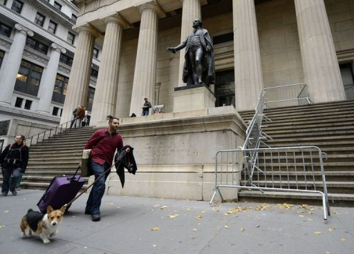 <p>A man walks up Wall Street past Federal Hall with his luggage and dog near the New York Stock Exchange October 28, 2012 as residents of lower Manhattan evacuate the city. The stock exchange will be closed completely Monday and possibly even Tuesday due to the imminent arrival of Hurricane Sandy, its operator said.</p>